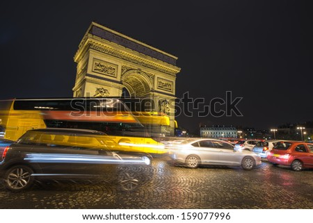 Paris traffic at night along Triumph Arc. Famous Etoile roundabout. - stock photo