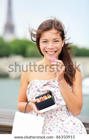 Paris woman eating macaroon with Seine and Eiffel Tower in background. Beautiful woman tourist holding macaroon box and shopping bag.
