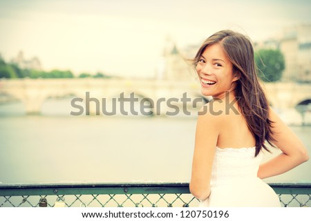 Paris woman laughing joyful and candid in Paris on brige on river Seine. Fresh energetic young mixed race Asian Caucasian female model joyful. - stock photo