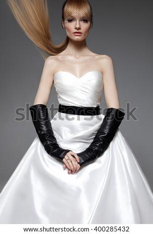 Parisian fashion bride model. White wedding dress. Blonde flying hair. Make up. Black gloves. Studio shot. Calm. - stock photo