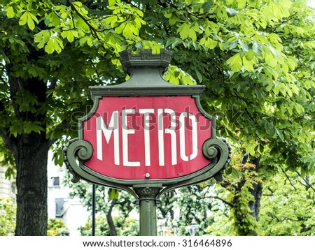 Parisian metro sign with a lamppost against old vintage wall - stock photo