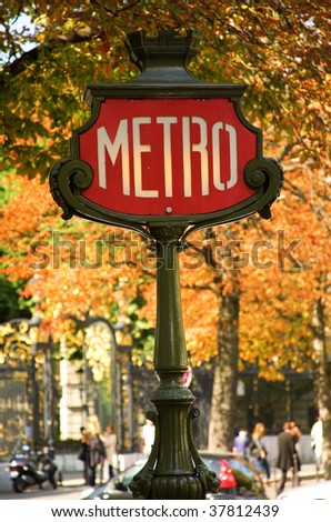 Parisian metro sign with autumn trees in the background