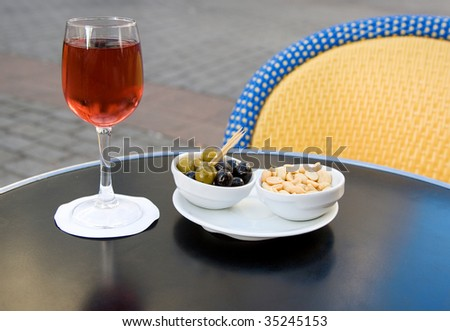 Parisian street cafe table with traditional French aperitif kir cassis and nibbles - stock photo