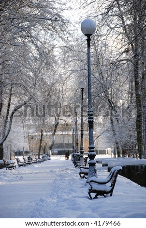 Park alley in winter with a row of benches