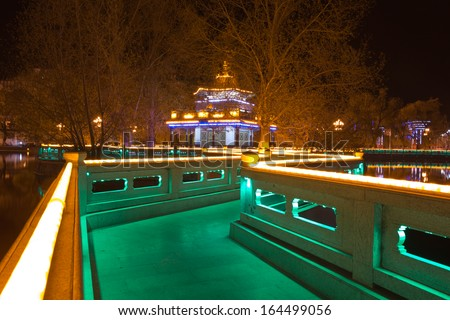 Park at night with illuminated led lights along the path around the pond at the Potala Square in Lhasa. Tibet 2013. - stock photo