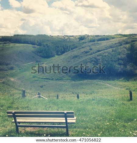 Park bench on hill overlooking lush summer park landscape.  Old fence and hiking trails.  Instagram effects.