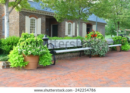 Park benches and flowers outside a public restroom along a red brick walkway on a nice summer day. - stock photo