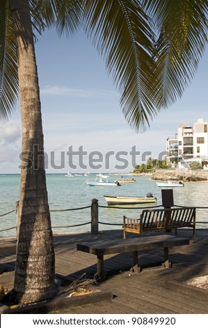 park benches boardwalk boats in  harbor St. Lawrence Gap Barbados Caribbean Sea