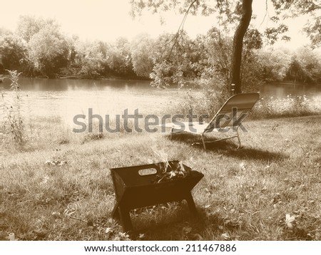 Park near the river - relaxing picnic, grilling, barbecue in sepia retro vintage - stock photo