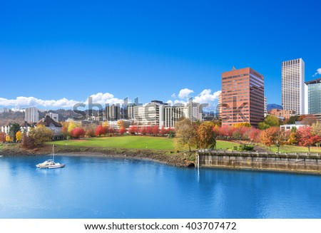 park near tranquil water with cityscape and skyline in portland - stock photo