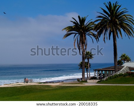 Park on a beach north of San Diego, California, with a couple resting on a bench. - stock photo