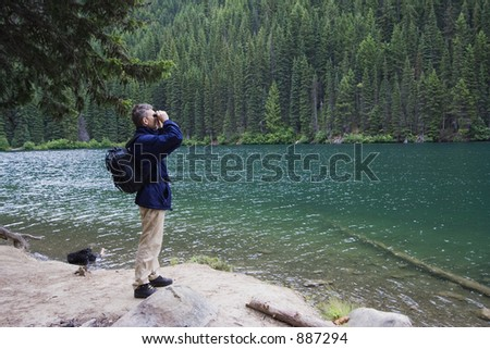 park ranger watching closely wildlife - with his field glass - adobe RGB - stock photo