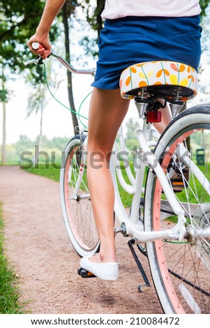 Park ride. Close-up rear view of young woman riding bicycle in park - stock photo