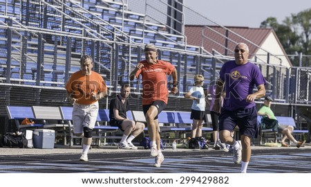 PARK RIDGE, ILLINOIS, USA - July 23, 2015: Three seniors sprint in a 50-meter dash on a high-school track during the Six-County Senior Games, sponsored by the Illinois Park and Recreation Association. - stock photo