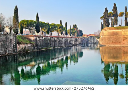 Park with channel and cypress trees, beautiful Peschiera del Garda, Italy. - stock photo