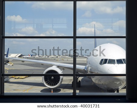 Parked aircraft on an airport through the gate window.