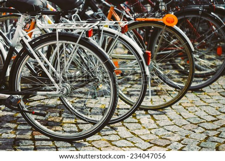Parked Bicycles On Sidewalk. Bike Bicycle Parking In Big City. Toned Instant Photo - stock photo