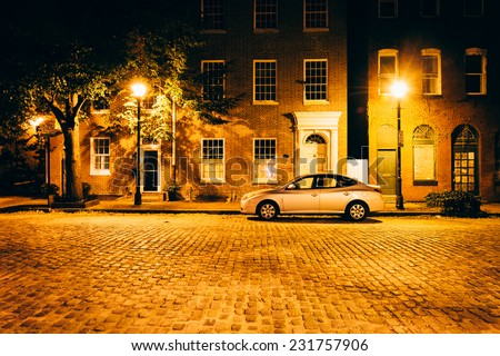 Parked car in front of brick buildings on a cobblestone street at night in Fells Point, Baltimore, Maryland. - stock photo