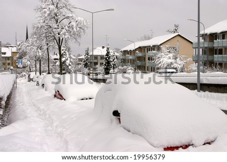 Parked cars buried under snow