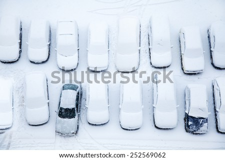 Parked cars covered in snow shot from above - stock photo
