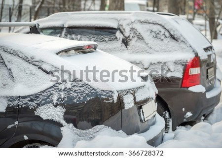 parked cars covered with fresh white snow - stock photo