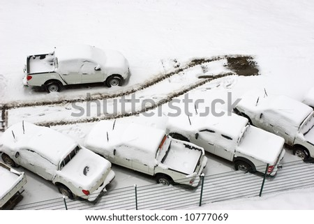 Parked cars under snow at parking lot with tracks of one gone car aerial view - stock photo