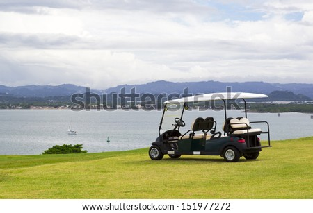 parked golf cart facing water reservoir with dramatic cloudy sky - stock photo