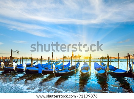 Parked gondolas on Piazza San Marco and The Doge's Palace embankment and sunset sunshine (Venice, Italy) - stock photo