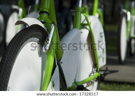 Parked, green and white rental bikes. Very shallow depth of field, with only parts of the nearest bike in focus.