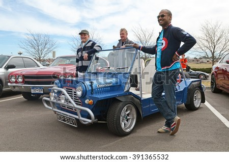 PARKER, COLORADO - MARCH 12, 2016: People pose with a Mini Moke car having license plate issued in Reading, UK in early 1980s. Cars and Coffee Denver is a monthly gathering of auto enthusiasts
