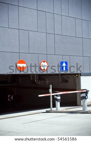 Parking garage entrance and exit with gate barrier - stock photo