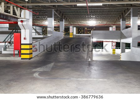 Parking garage interior, neon lights in dark industrial building, modern public construction - stock photo