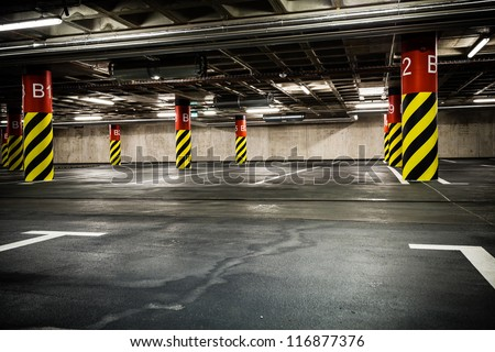 Parking garage underground interior. Bright neon light in industrial building basement, steel and concrete. - stock photo