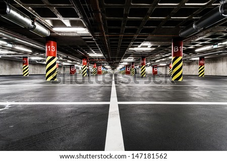 Parking garage underground interior, neon lights in dark industrial building, modern public construction - stock photo