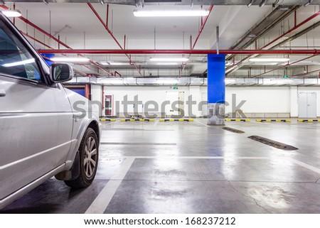 Parking garage, underground interior with a few parked cars - stock photo