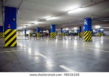 Parking garage, underground interior with a few parked cars. Neon light in bright industrial building. - stock photo