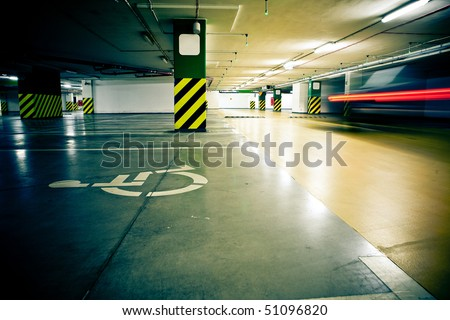 Parking garage, underground interior with car in motion blur - stock photo