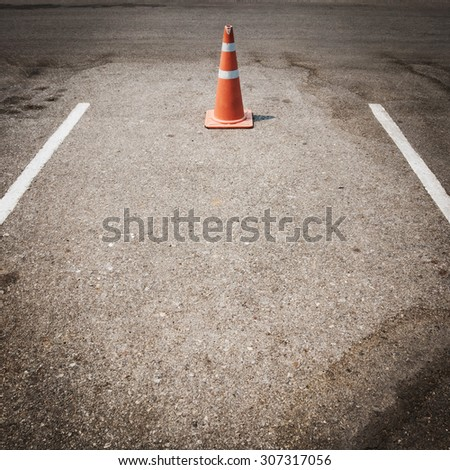 parking lot with traffic cone on street used warning sign on road - stock photo