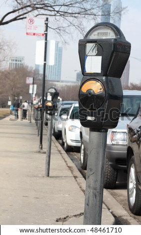 Parking meter in the city and a row of cars - stock photo