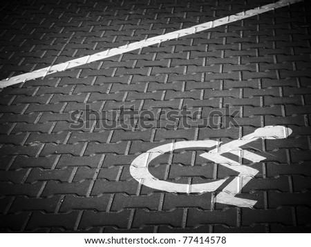 Parking place sign for disabled on grey dark brick - stock photo
