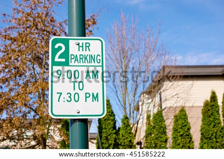 Parking sign posted for two hours only off a city street.