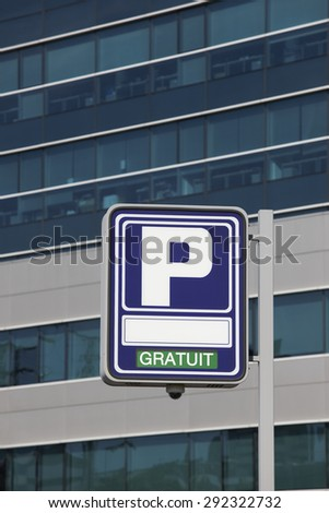 Parking signpost with gratuit text and modern building background. Vertical