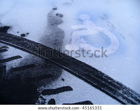 Parking space for disabled at wintertime. - stock photo
