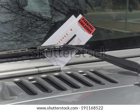 parking ticket on motor car windscreen or windshield.  - stock photo
