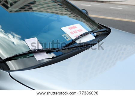 """Parking ticket placed under windshield wiper of a car.  There is also also warning sign that there is a """"boot"""" attached to a wheel and the car cannot be driven until the fine is paid - stock photo"""
