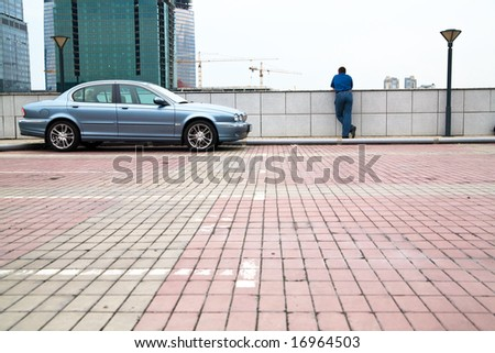 Parking with man looking at view and his luxurious car.