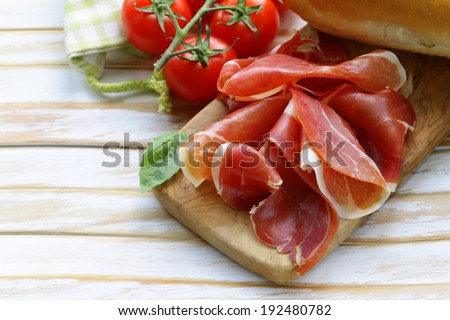 parma ham (jamon) sliced on a wooden board - stock photo