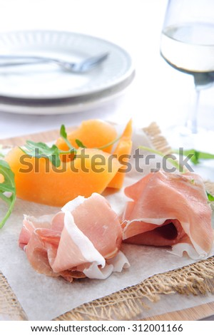 Parma ham served with rockmelon, a common Italian antipasto with a glass of wine  - stock photo