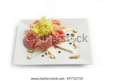Parma ham with the goat cheese and pistachios on a light plate on a white background - stock photo