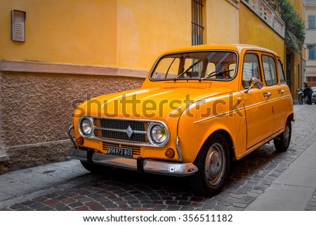 PARMA, ITALY - DECEMBER 22, 2015: Retro orange Renault 4TL car  parked at the old stone street over yellow wall in Parma, Italy. - stock photo
